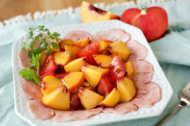 A spicy twist on peach and tomato salad. I make my dressing with lime juice and fresh ginger over ripe peaches and tomatoes