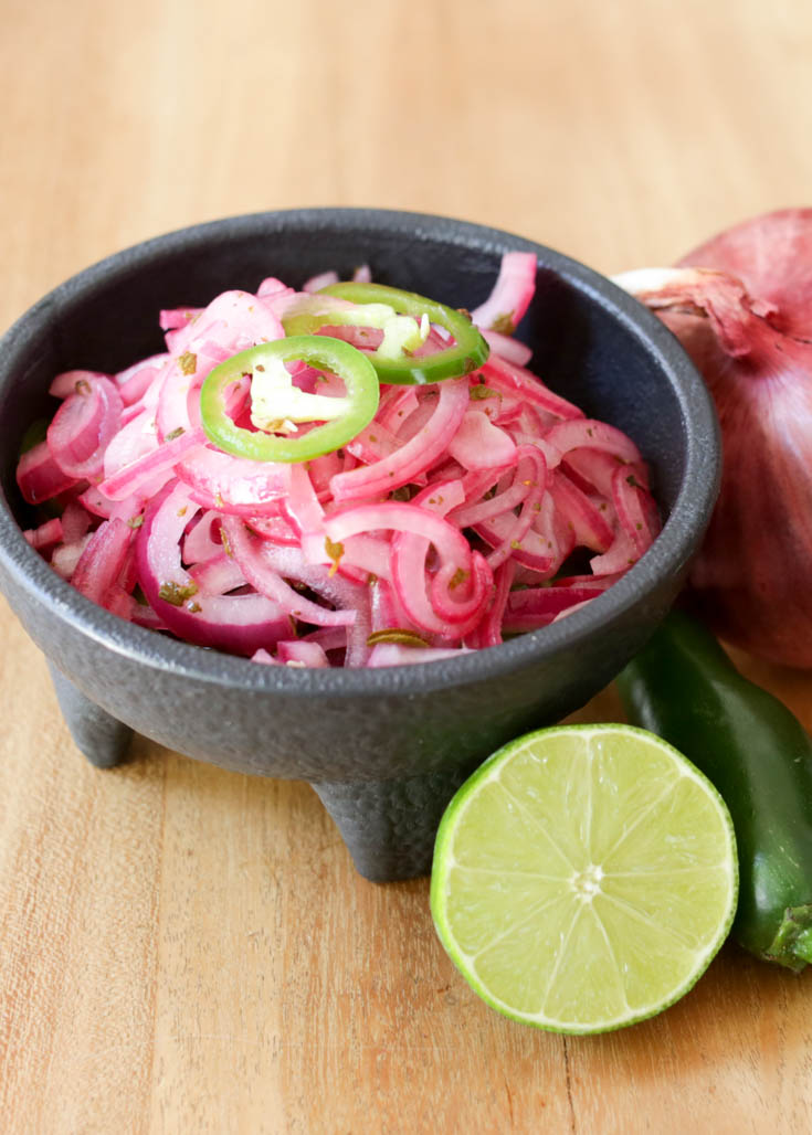 Quick pickled red onions with lime juice, salt, oregano and jalapeños makes a simple taco condiment