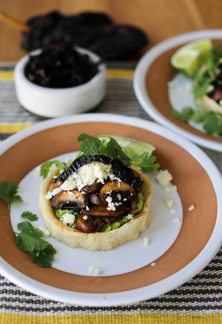 Vegetarian sopes with guacamole, sauteed mushrooms, crisp fried ancho chile strips and cotija cheese. Easily converts to a vegan sopes recipe, too! Sopes are a thick corn tortilla shell filled with anything you like and they make an easy weeknight meal.