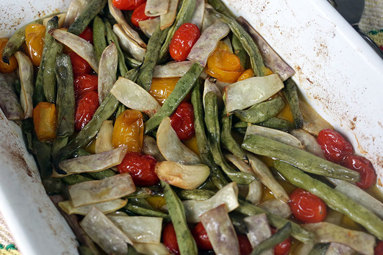 Roasted fresh green beans with cherry tomatoes, olive oil, garlic and salt. A simple side dish or vegan mean dish served with pasta
