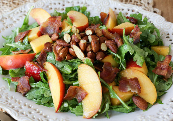 Wonderful main-dish summer salad with fresh peaches or nectarines, crispy bacon, toasted almonds, and arugula in a simple, homemade honey mustard dressing